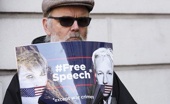 Мужчина стоит с плакатом в поддержку Джулиана Ассанжа в Лондоне