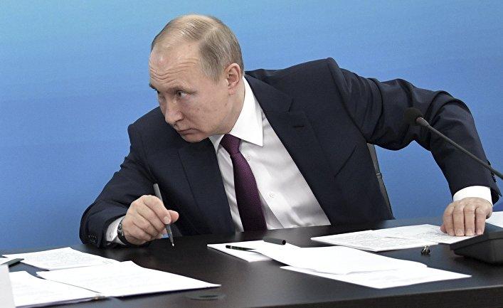 Президент России Владимир Путин работает за столом