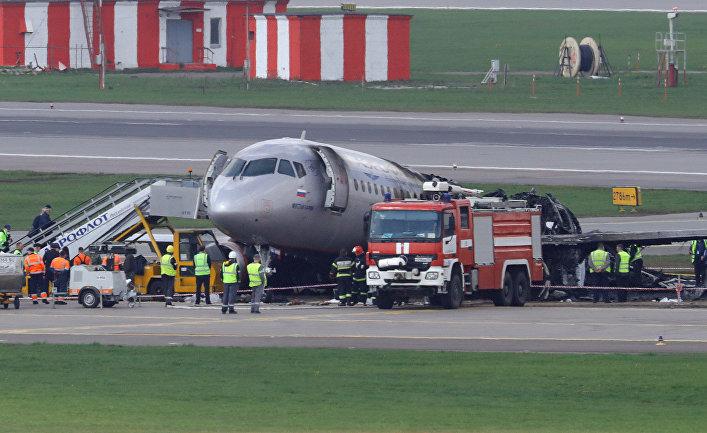 Сотрудники экстренных служб на месте аварии пассажирского самолета Sukhoi Superjet-100 в аэропорту Шереметьево