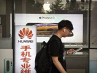 Прохожий на фоне витрины магазина электроники в Пекине