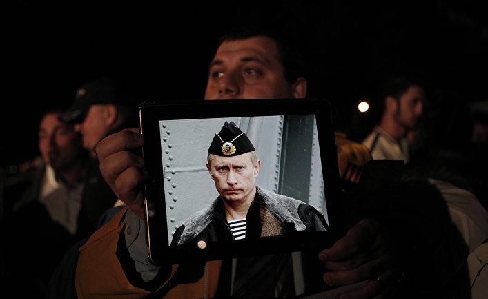 Протестующие с фотографией президента России Владимира Путина во время акции протеста у здания кипрского парламента