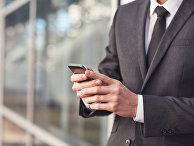 Мужчина в костюме пользуется смартфоном