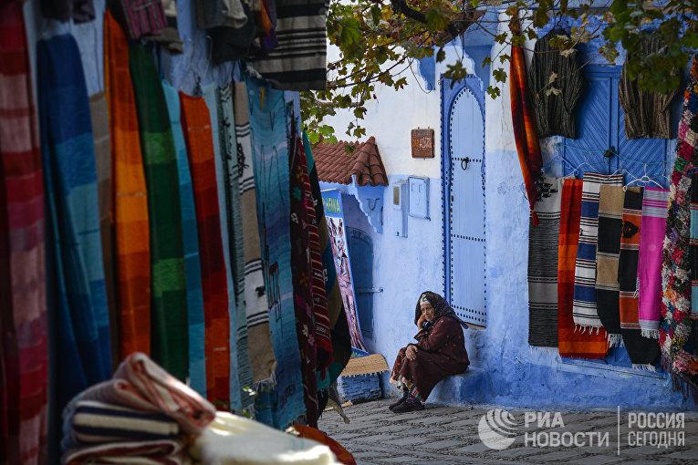Женщина сидит на ступенях своего дома на одной из улиц города Шефшауэн