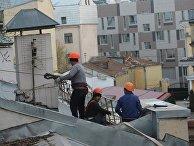 Рабочие-строители на крыше здания в Москве