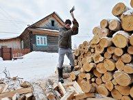 Мужчина рубит дрова в деревне