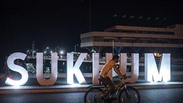 Парень катается на велосипеде на набережной Сухума.