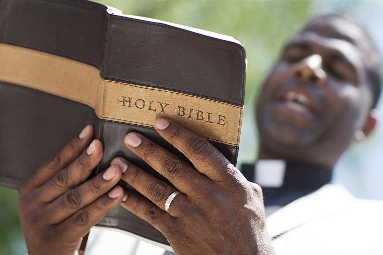 Пастор читает молитву, посвященную жертвам стрельбы в афроамериканской церкви Чарльстона