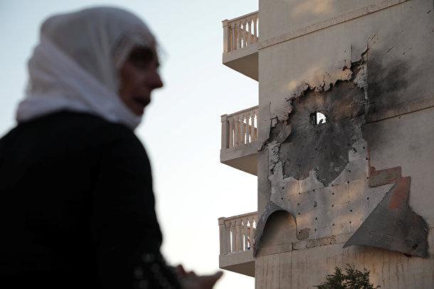 Женщина у дома, который был поврежден ракетой