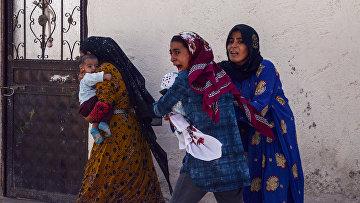 Женщины покидают свои дома в городе Акчакале во время обстрела города