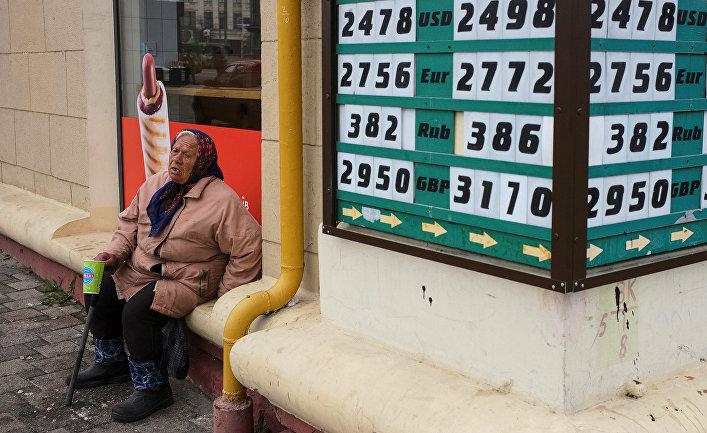 Попрошайка возле пункта обмена валют в центре Харькова