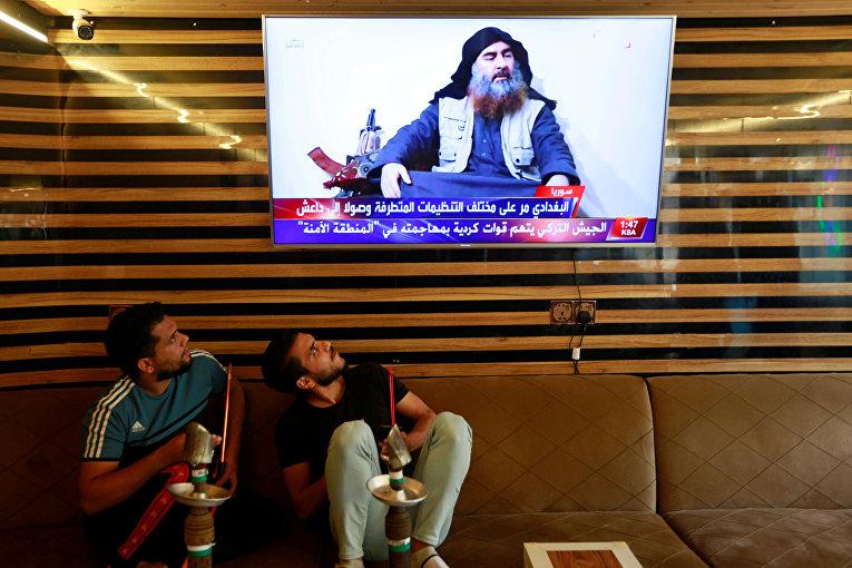 Молодые люди в Ираке смотрят репортаж об уничтожении Абу Бакра аль-Багдади