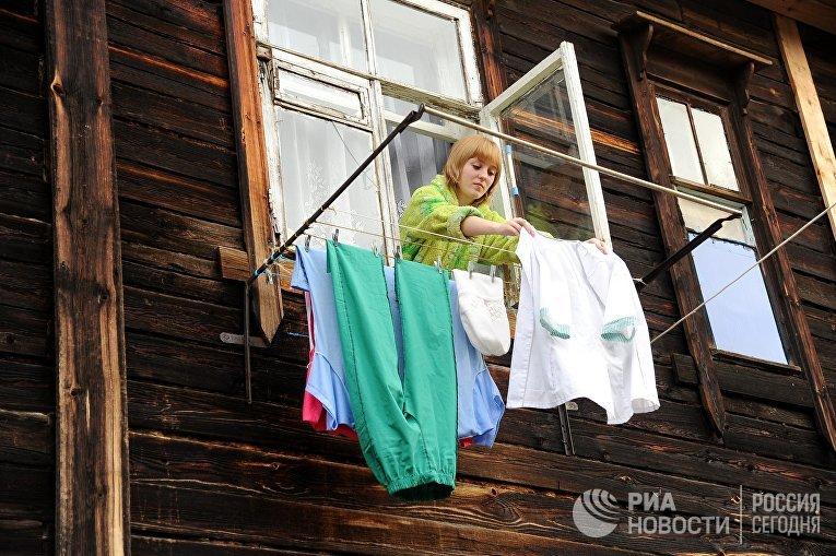 Женщина вешает белье в своем доме