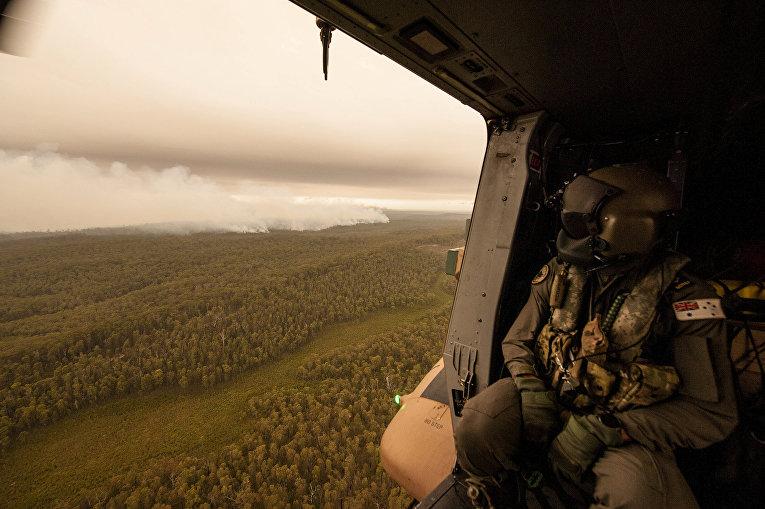 Член экипажа вертолета ВМФ Австралии наблюдает за пожарами у реки Канн в Гипсленде, Австралия