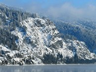 Покрытый снегом крутой таежный берег реки Енисей