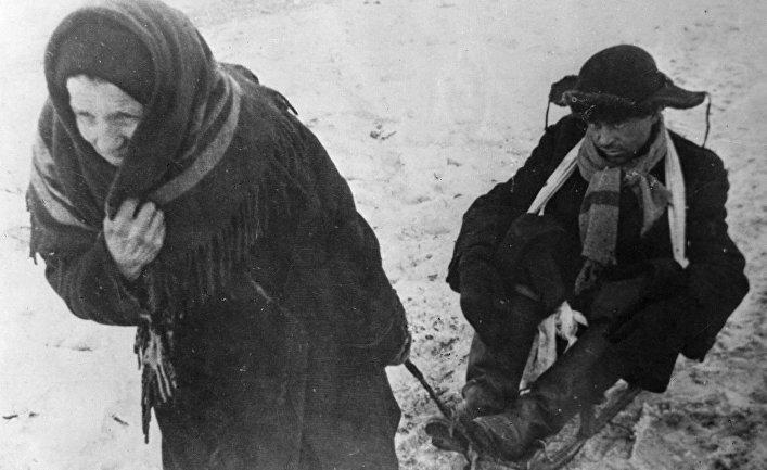 Жители блокадного Ленинграда: женщина везет ослабевшего от голода мужа на санках