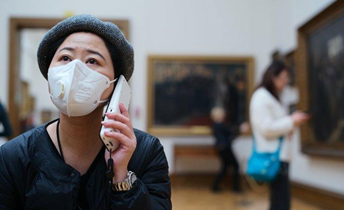 Посетительница музея в медицинской маске