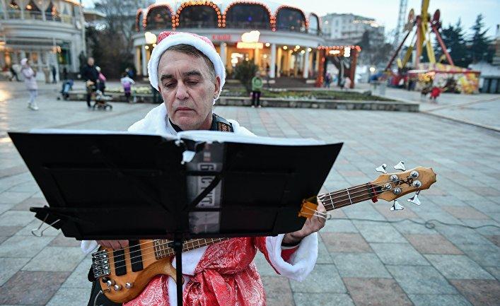Музыкант в костюме Деда Мороза выступает на набережной в Ялте, Крым