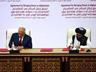 Мулла Абдул Гани Барадар и Залмаем Халилзад на церемонии подписания соглашения в Дохе, Катар