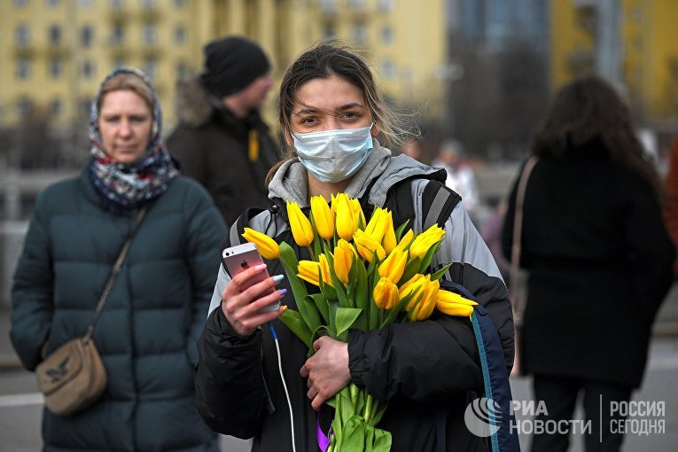 Девушка с цветами и в маске на Пушкинской набережной в Парке Горького в Международный женский день в Москве