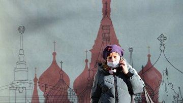 Женщина в медицинской маске на одной из улиц в Москве