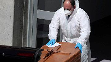 Работник похоронного бюро в защитном костюме перемещает гроб с телом погибшего от коронавируса, Испания