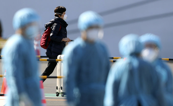 Пассажир и медицинский персонал в порту Иокогамы, недалеко от Токио