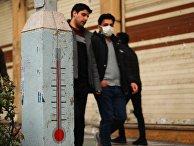 Молодые люди в медицинских масках на одной из улиц Ирана во время эпидемии коронавируса