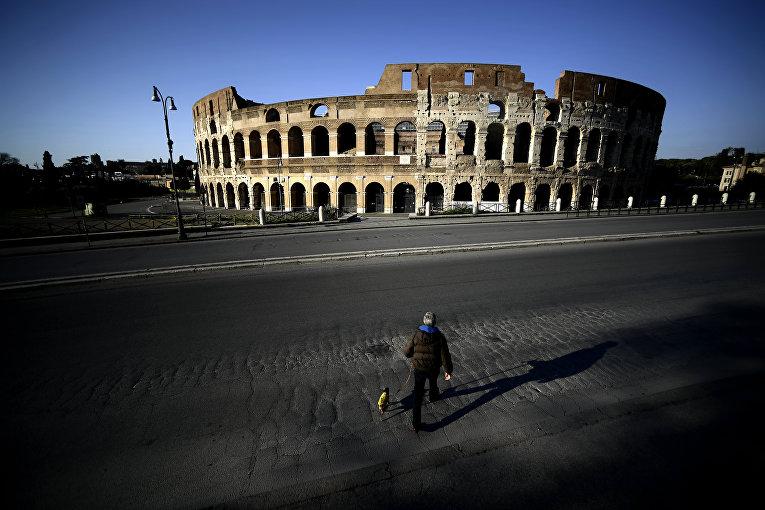 3 апреля 2020. Мужчина с собакой рядом с Колизеем во время карантина в Риме, Италия