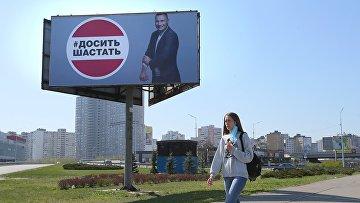Девушка у рекламного щита, установленного в Киеве в связи с коронавирусом. Надпись: «Хватит шастать»
