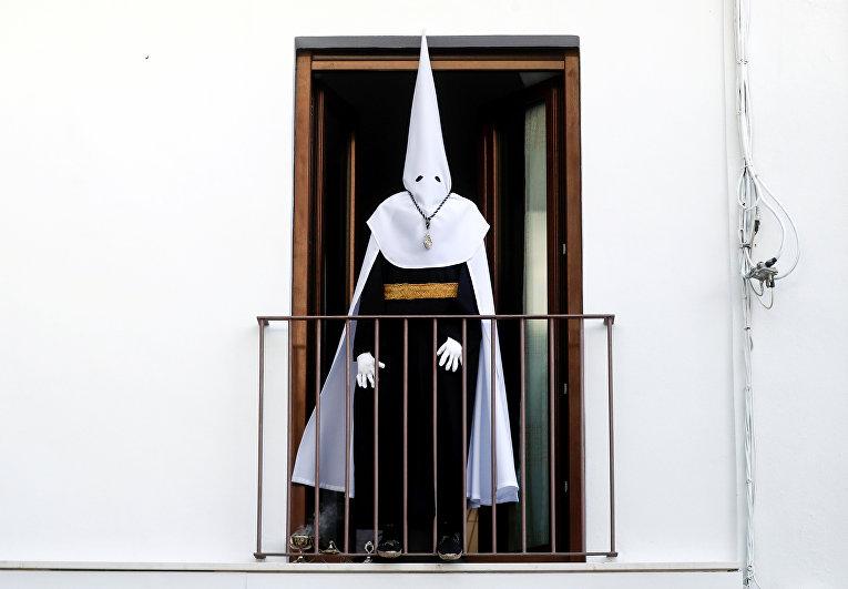 Испанец в костюме для ежегодного пасхального шествия на балконе во время карантина в Ронде, Испания