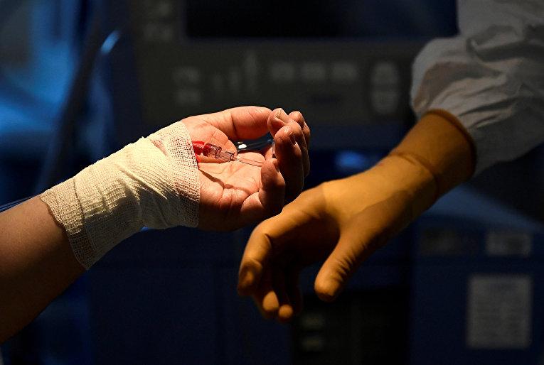 9 апреля 2020. Руки пациента с коронавирусом и медика в больнице Варезе, Италия