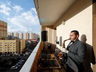 Саксофонист Игорь Ермошкин выступает на балконе жилого дома в Ставрополе