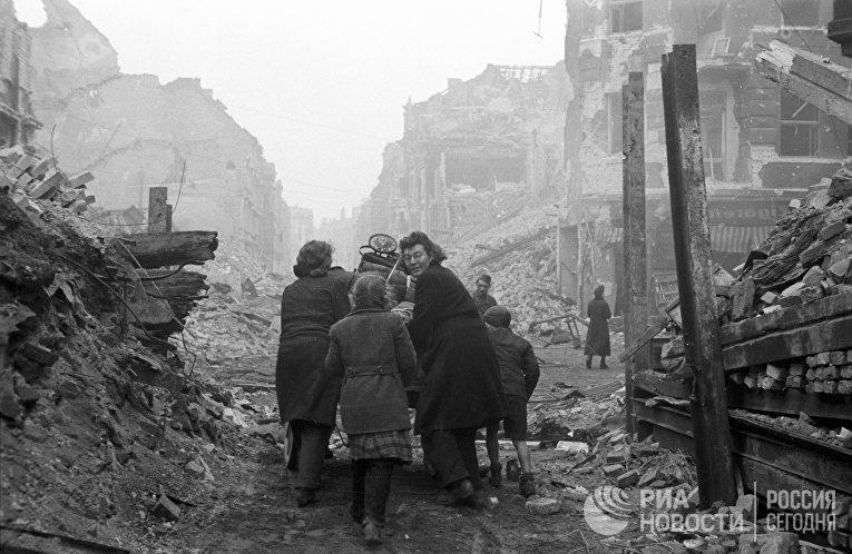 Жители Берлина возвращаются домой по заваленной обломками улице. Бои закончились.