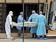 Медики выносят тело пациента, умершего от коронавируса в Ахмадабаде, Индия