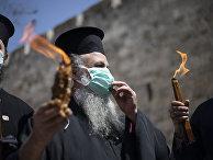 Православные священнослужители несут Благодатный огонь в Иерусалиме