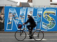 Велосипедист  на фоне граффити в поддержку врачей в Белфасте