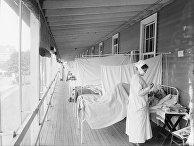 Медсестра ухаживает за пациентом во время эпидемии испанки, 1918-1919