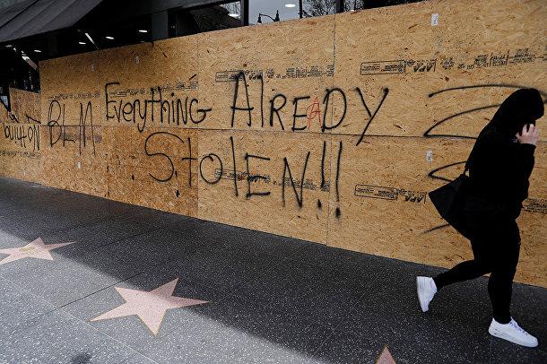 Надпись «все уже украдено» на закрытой фанерой витрине магазина в Лос-Анджелесе