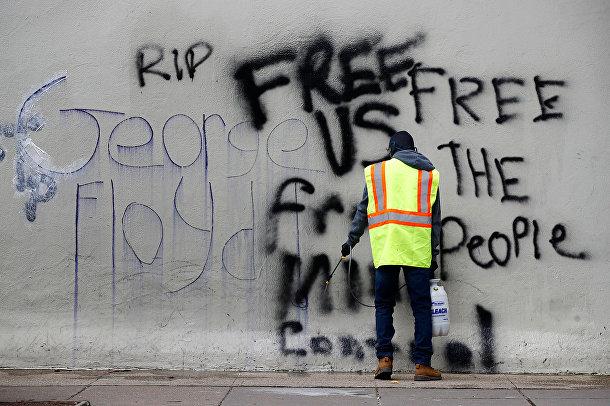 Рабочий смывает граффити в Вашингтоне