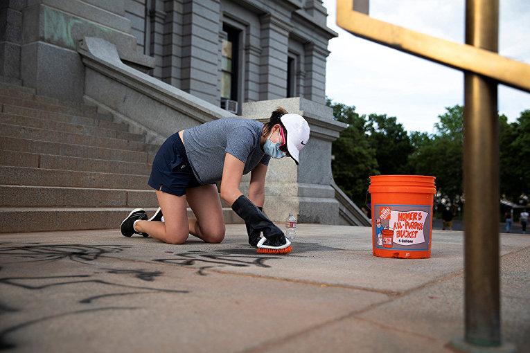 Волонтер убирает граффити в Денвере