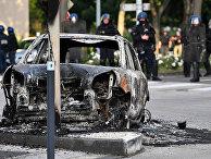 Жандармы возле сгоревшего автомобиля в Дижоне