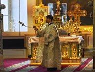 Священнослужитель во время богослужения в Казанском кафедральном соборе в Санкт-Петербурге, открывшемся после карантина