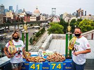 Рекордсмен мира среди мужчин Джои Честнат и рекордсмен среди женщин Мики Судо во время официальной церемонии взвешивания для конкурса по поеданию хот-догов в Нью-Йорке
