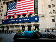 Мужчина спит на скамейке возле Нью-Йоркской фондовой биржи