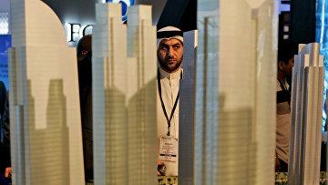 Араб рассматривает макет строительного проекта в финансовом районе Дубая, ОАЭ