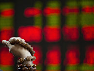 Мужчина перебирает четки на фондовой бирже в Пекине