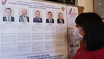 Женщина около информационного стенда во время досрочного голосования на выборах губернатора Краснодарского края