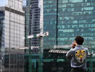 Молодой человек на набережной Тараса Шевченко в Москве смотрит на Москва-сити