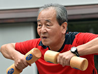 Пожилой мужчина во время занятий с деревянными гантелями в Токио