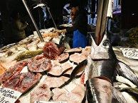 Продавец на рыбном рынке Риальто в Венеции